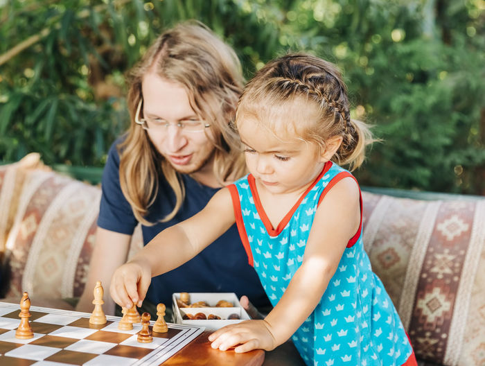 Father and daughter playing chess outdoors