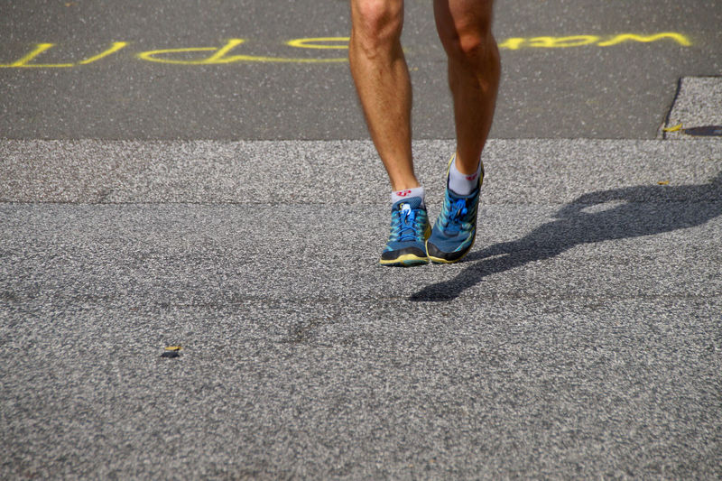 Low Section Of Man Running On Footpath During Marathon