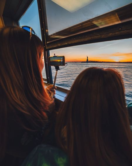 Rear View Of Women In Ferry Boat While Looking At Statue Of Liberty