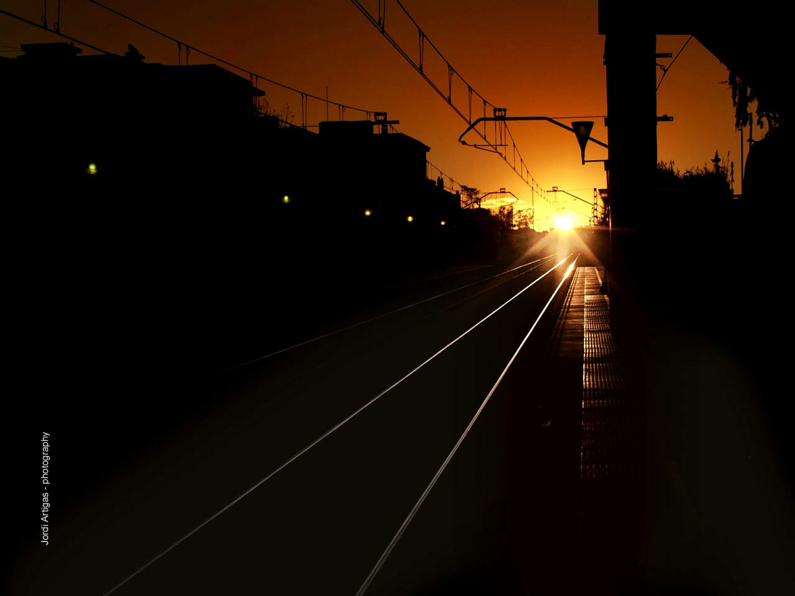 railroad track, transportation, sunset, rail transportation, power line, electricity pylon, the way forward, electricity, diminishing perspective, vanishing point, illuminated, cable, silhouette, connection, public transportation, power supply, sky, railroad station, railroad station platform, long
