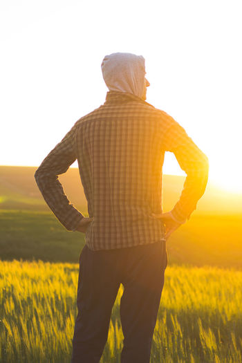 Rear View Of Man Standing By Grassy Field Against Clear Sky During Sunset