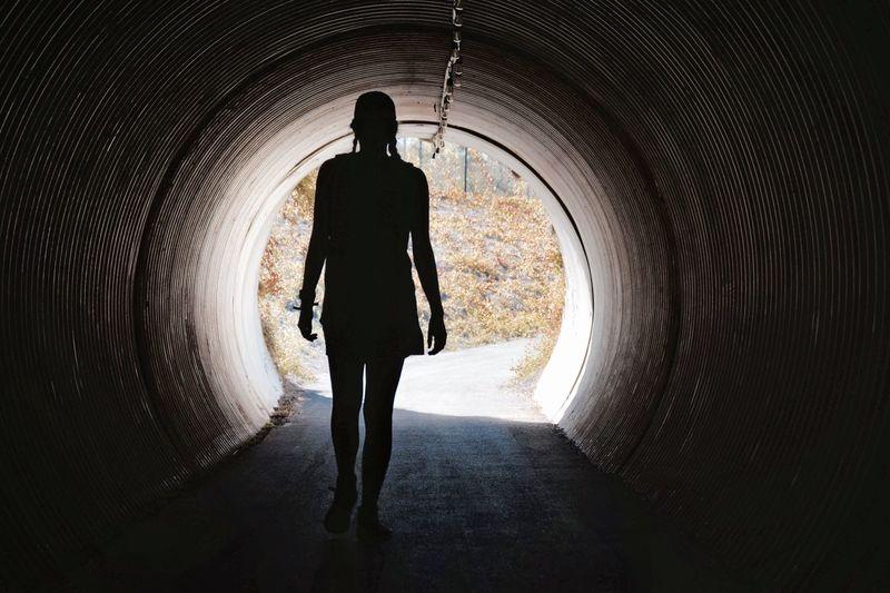 Silhouette Woman Walking In Tunnel