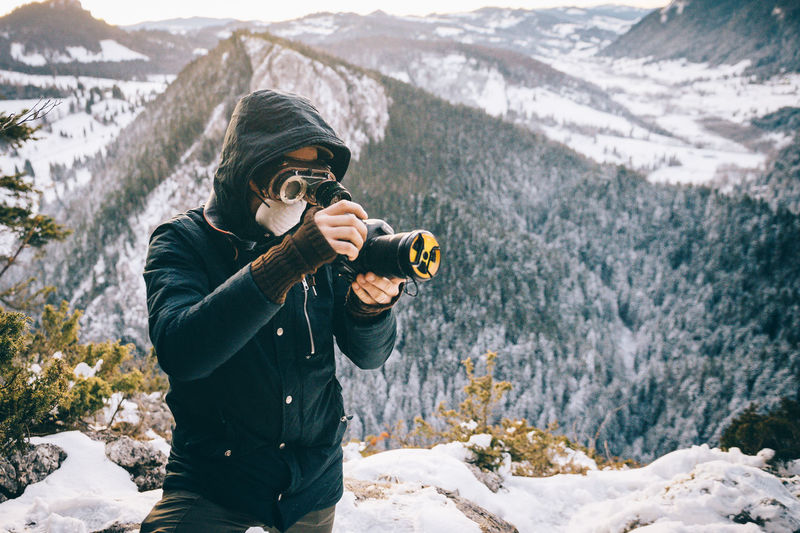 Woman photographing on snow covered mountain