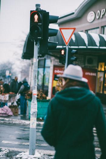 Rear view of a man walking on street in city