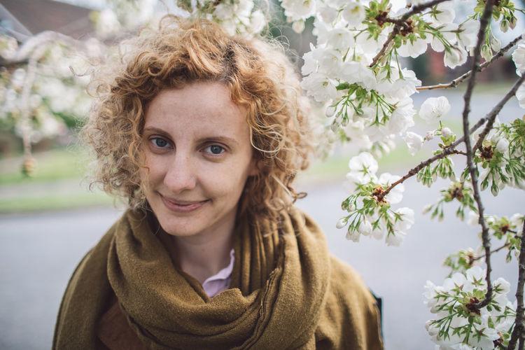 Portrait of woman against blooming flowers