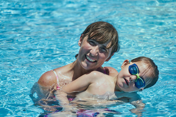 Portrait of a smiling young man swimming in pool