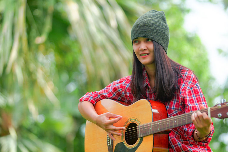 Thoughtful young woman playing acoustic guitar against trees