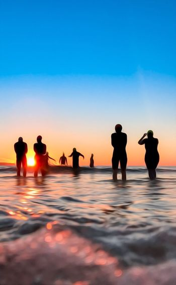 Silhouette people on sea shore against sky during sunset
