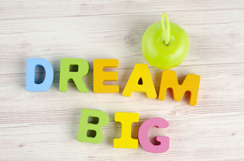 Business success concept, DREAM BIG word on wooden desk over blue background Text Table Still Life Alphabet Letter Indoors  Western Script Wood - Material Capital Letter Directly Above Communication Childhood Multi Colored Toy Number High Angle View Plastic Yellow Green Color