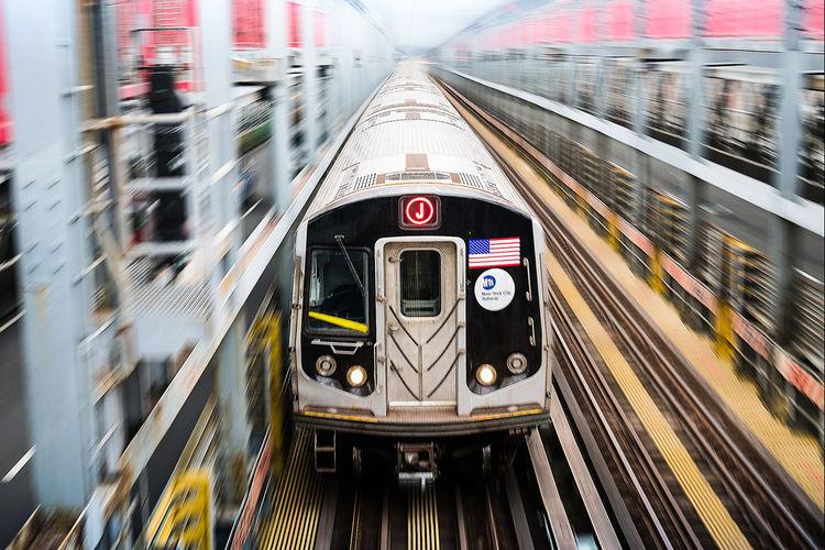 Metro train over railroad tracks