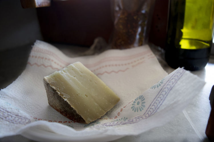 wedge of sardinian pecorinowith in background a bottle of red wine Hard Pecorino Aged Cheese Fiore Sardo Matured Milk Sardinian Sardo Semi-dark Sheep Wedge