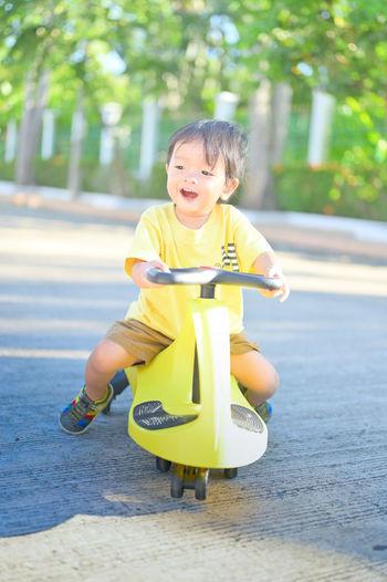 Portrait of cute boy sitting on yellow playing