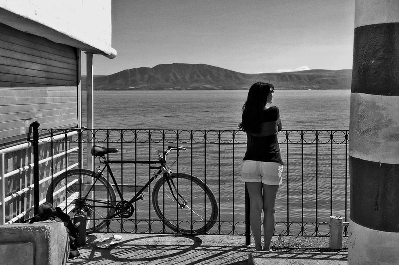 Man with bicycle on railing by sea against sky