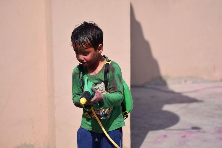 Boy playing with squirt gun during holi