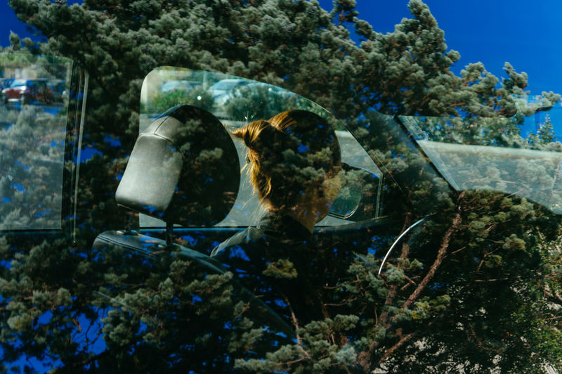 Portrait of the Woman Sitting in the Car through the Window with Reflection of Tree Branches and a Blue Sky Woman Portrait Car Tree Branches Sky Reflection Thoughts Vehicle Driving Sitting Blue Green Feelings EyeEm Best Shots EyeEmNewHere Portrait Of A Woman Fine Art Photography Contemporary Art
