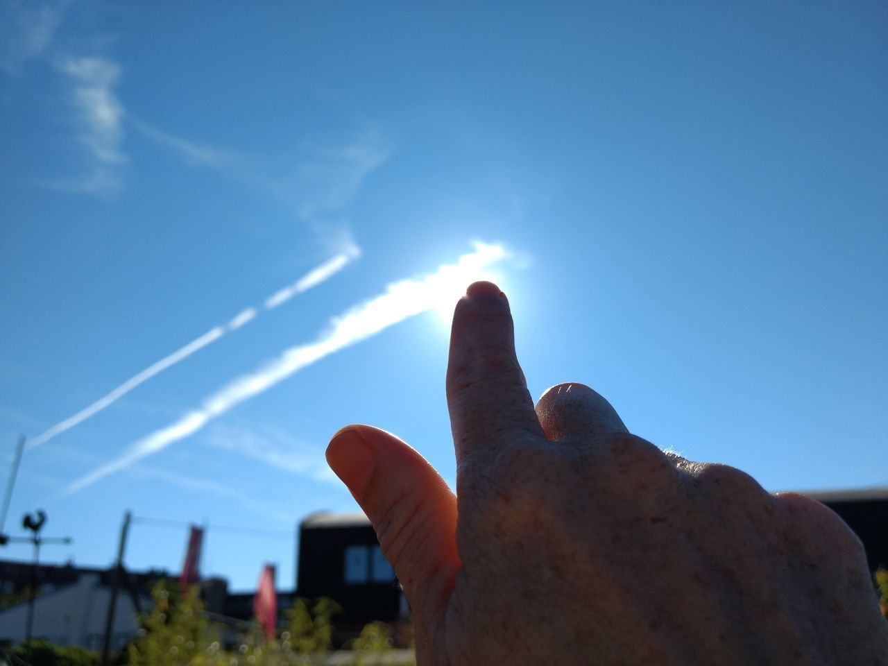 CLOSE-UP OF PERSON HAND AGAINST SKY