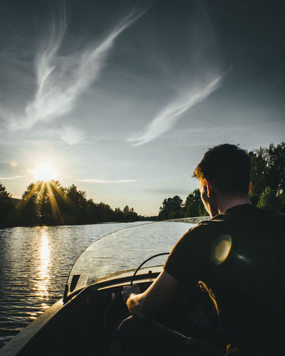 Rear view of man riding speedboat against sky during sunset
