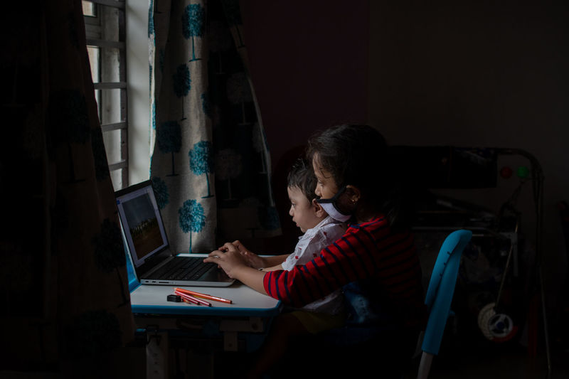 Rear view of child playing on laptop at home