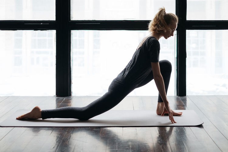 Women practice yoga in the loft One Person Yoga Pose Yoga Sports Clothing Relaxation Exercise Women Wellbeing Full Length Window Real People Lifestyles Side View Healthy Lifestyle Exercising Hairstyle Hair Stretching Indoors  Sport Loft Practicing