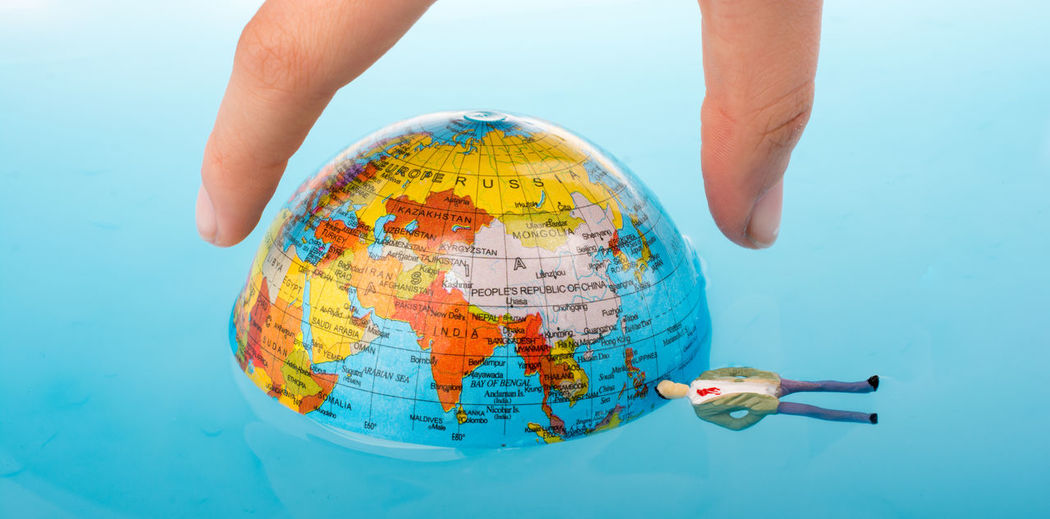 Cropped hand holding globe in swimming pool