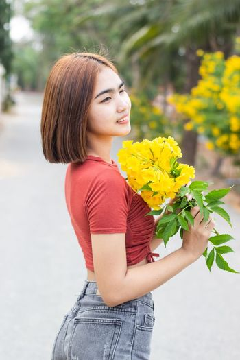 Young woman holding yellow while standing by flower