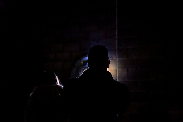 Rear view of silhouette man standing against wall