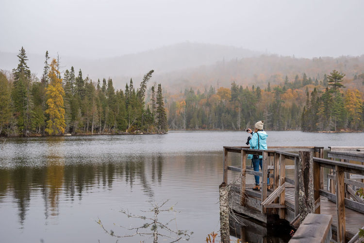 Man standing on lake against trees