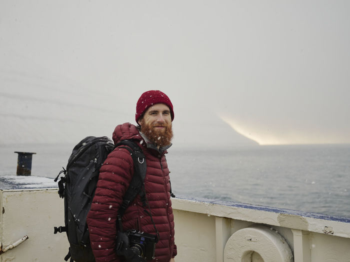 Portrait of man standing by sea against sky during winter