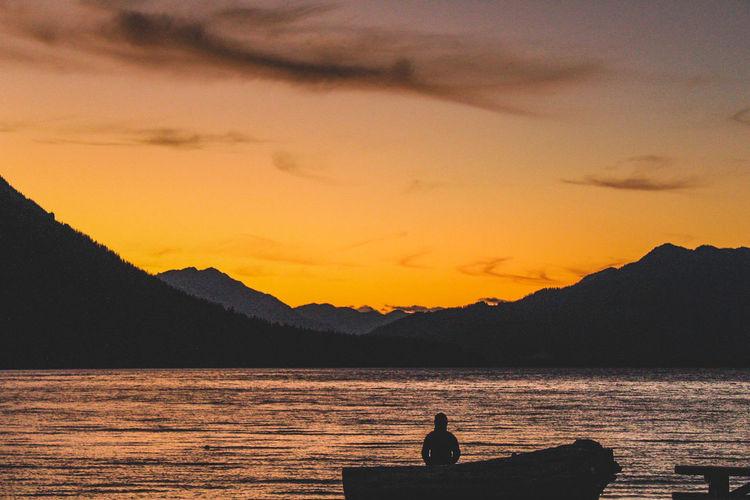 Silhouette people sitting on mountain against orange sky