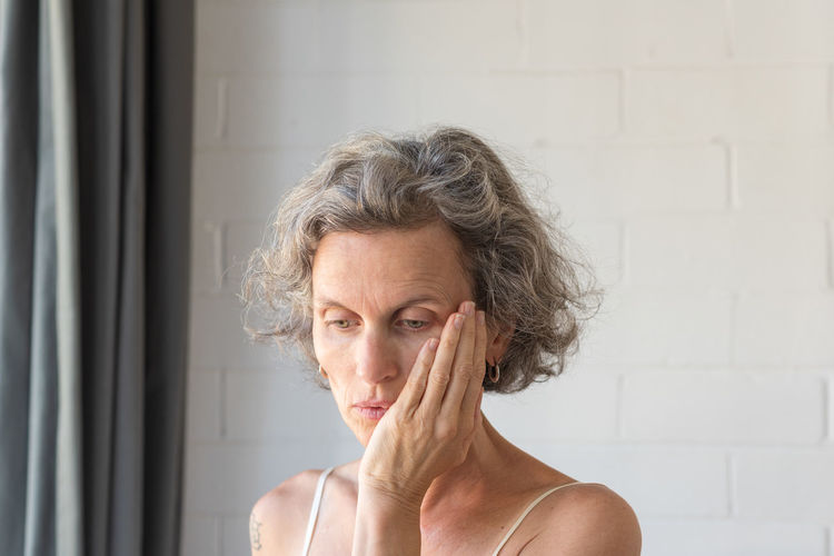Woman with hand on face Headshot Portrait One Person Adult Indoors  Front View Lifestyles Women Worried Real People Senior Adult Mature Adult Emotional Stress Sadness Senior Women Emotion Close-up Short Hair Contemplation Depression - Sadness Hairstyle