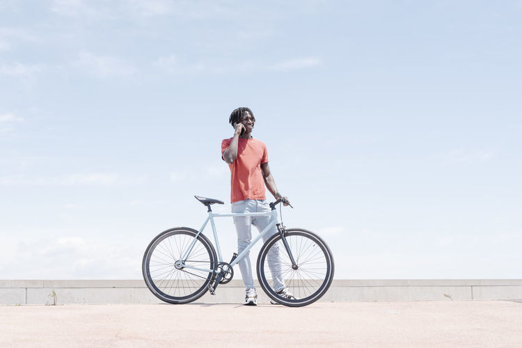 Full length of woman sitting on bicycle against sky