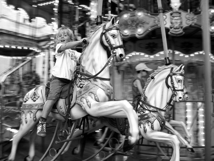 Portrait of cheerful boy sitting on carousel horse in amusement park