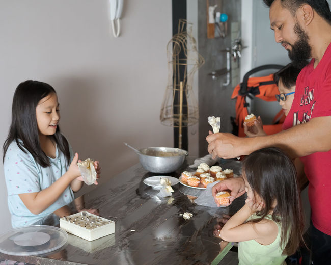 Father with children making sweet food on table at home