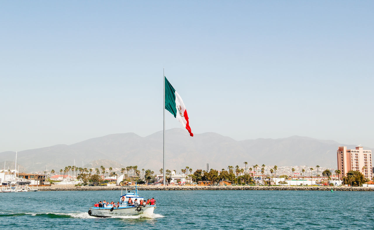 flag, water, mountain, day, transportation, clear sky, mode of transport, nautical vessel, patriotism, waterfront, sea, nature, outdoors, architecture, built structure, real people, beauty in nature, building exterior, sky