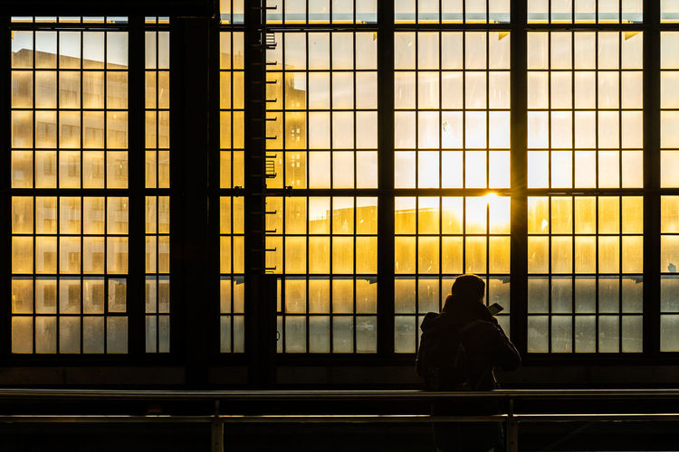 Man sitting by window during sunset