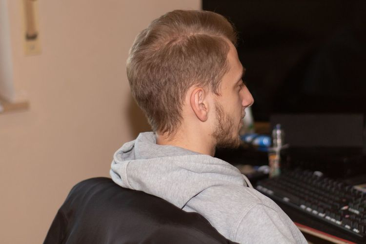 Musician looking at computer in recording studio