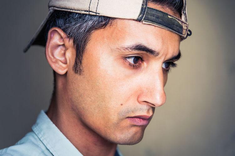 Close-up of thoughtful man wearing cap