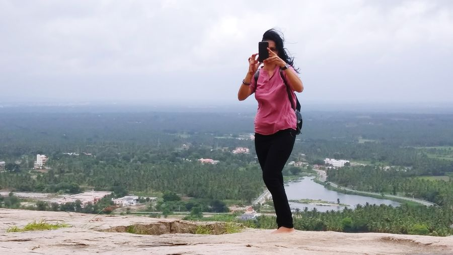 Full Length Of Woman Photographing With Mobile Phone While Standing On Mountain Against Sky