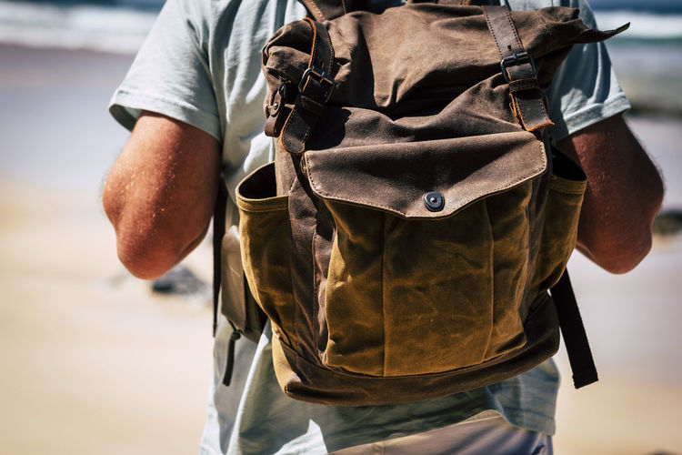 Midsection of man wearing backpack at beach