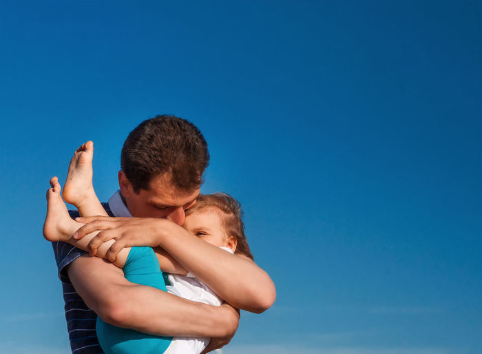 Father embracing with cute girl against sky outdoors