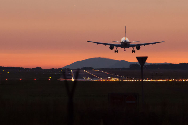 Airplane landing on sunset. Budapest, Hungary Air Air Vehicle Aircraft Wing Airplane Airport Airport Fence Commercial Airplane Fence Flying Journey Mid-air Mode Of Transport Nature Night No People On The Move Orange Color Outdoors Public Transportation Runway Runway Lights Silhouette Sky Sunset Transportation