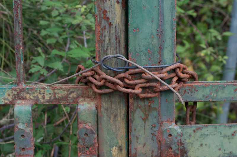 Close-up of rusty chain tied up on metal gate
