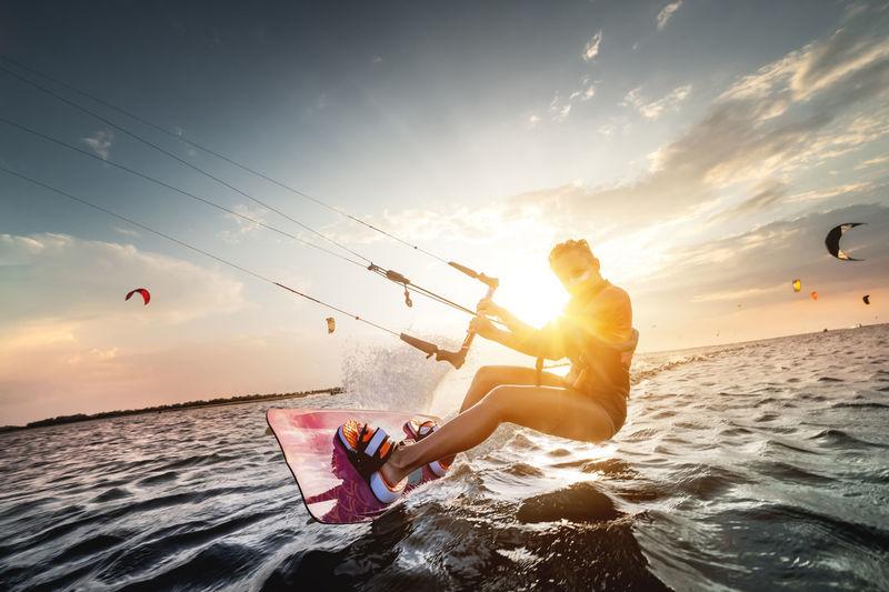 Woman kitesurfing against sky during sunset