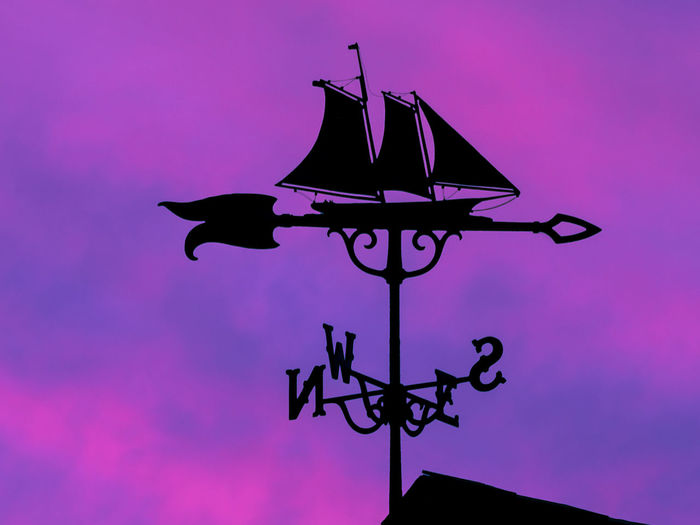 Low angle view of weather vane against sky during sunset