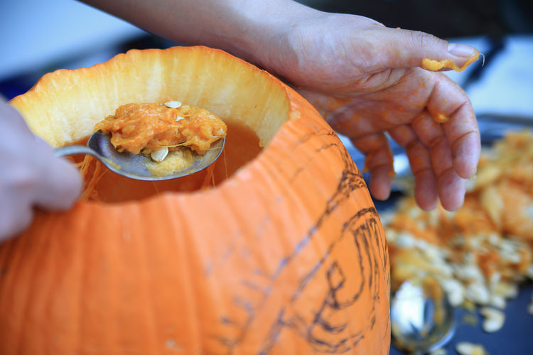 Cropped hand of man removing seeds from pumpkin for halloween