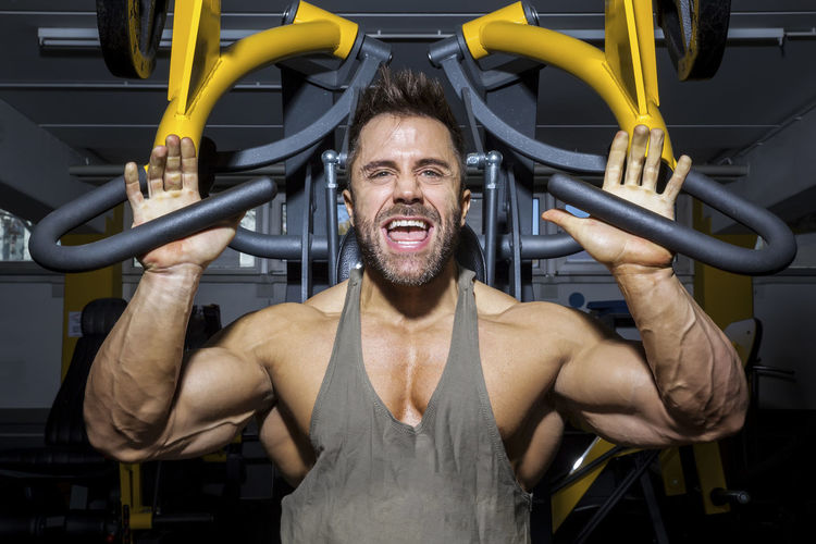 Portrait of man exercising on equipment at gym
