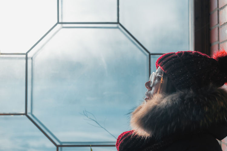 Young woman sitting by the window and looking at frozen glass Headshot One Person Real People Portrait Lifestyles Men Beard Day Adult Facial Hair Males  Leisure Activity Looking Window Sky Hat Architecture Close-up Outdoors Human Face Warm Clothing Architecture Winter Woman Depression - Sadness My Best Photo International Women's Day 2019