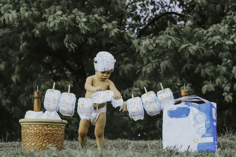 Shirtless boy drying diapers on land