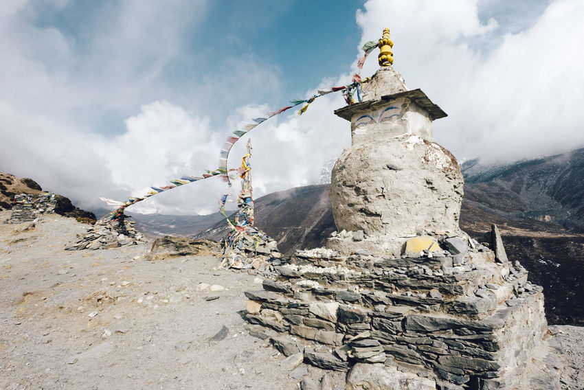 EBC Trek, Nepal Dramatic Sky Himalayas The Week on EyeEm Architecture Art And Craft Belief Cloud - Sky Day Flags Human Representation Male Likeness Mountain Nature No People Outdoors Place Of Worship Religion Representation Rock Rock - Object Sculpture Sky Solid Spirituality Statue