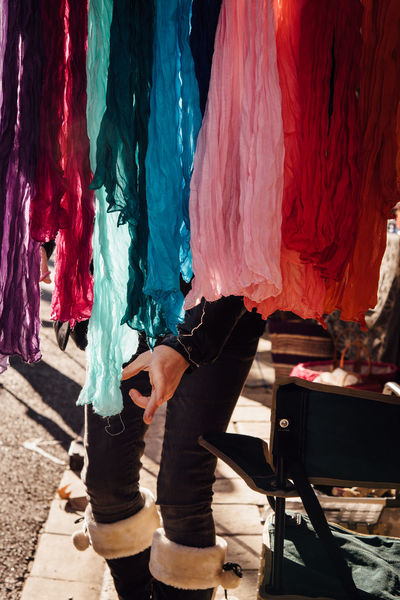 Choice Choosing Colors Life Market Shopping Adult Buying Day Headscarf Human Body Part Human Hand Human Leg Leisure Activity Lifestyles Low Section Market Stall Men One Person Outdoors People Performance Real People Scarf Women